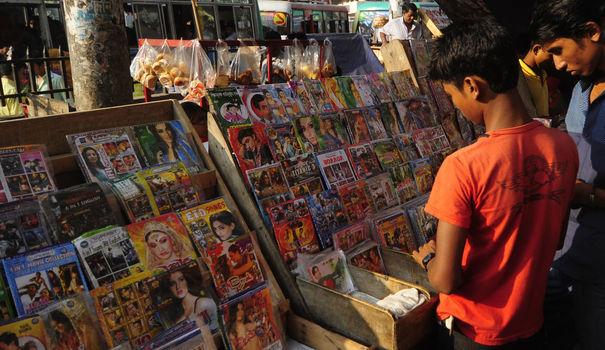 des-jeunes-gens-devant-un-stand-de-dvd-cd-et-magazines-dans-une-rue-de-dacca_4689920