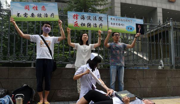 deguisee-en-infirmiere-xiao-tie-directrice-du-centre-lgbt-de-pekin-fait-mine-de-faire-une-injection-a-un-faux-patient-lors-d-une-manifestation-devant-un-tribunal-de-haidian-a-pekin-le-31-juillet-2014_5005647