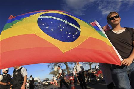 "A gay activist carries a Brazil flag in rainbow colours in protest at the ""March For Family"" demonstration against abortion and gay marriage, in front of the National Congress in Brasilia"