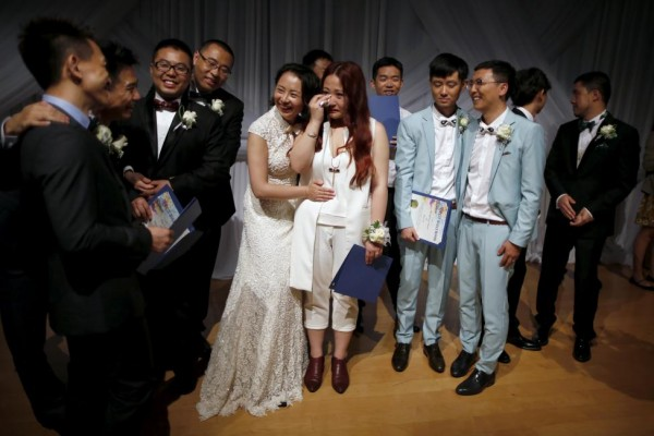 Xu Na hugs her new wife Xue Mengyao at a group wedding for same-sex couples in West Hollywood,