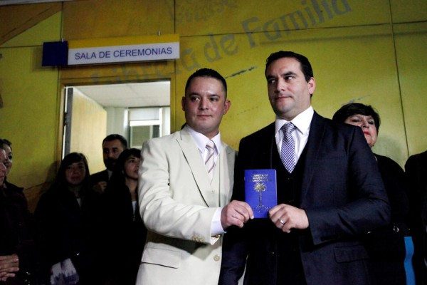 Chilean policeman Alcalde and Valdes show their civil union identification booklet following their civil union celebration in Santiago